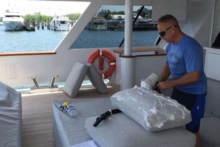 JC's Carpet Cleaning expert cleaning couch pillows on a superyacht deck.