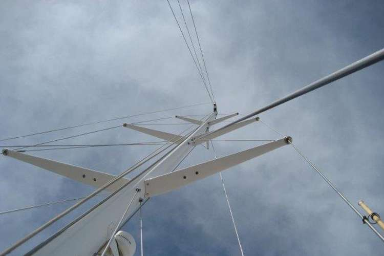 Image of a sailing mast taken on the deck of a boat with sky in the background.