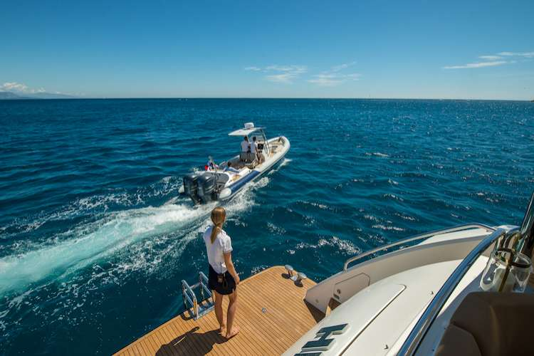 Woman standing on a superyacht swimming platform and Ribeye tender cruising next to it