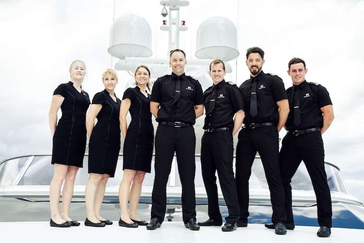Superyacht crew of seven people wearing black uniforms