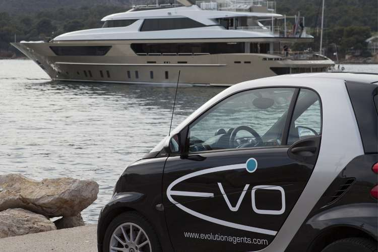 Evolution Yacht Agents car parked in a port with a superyacht in the background.
