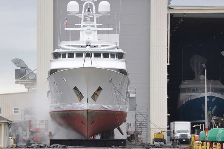 A ship dry docking in front of a shipyard hangar