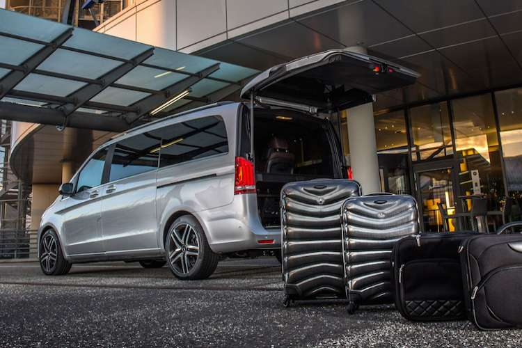 Luggages next to a silver Mercedes van